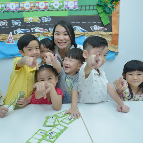 Smiling teacher and children in class pointing at camera