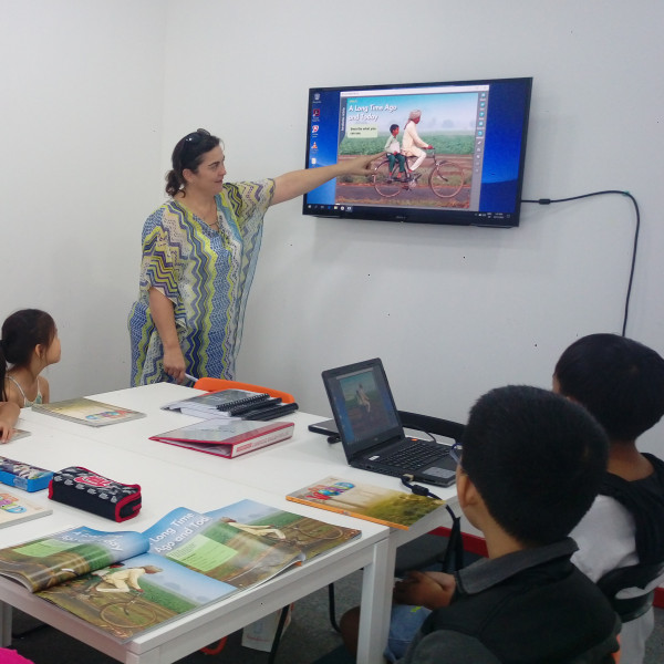 Teacher teaching students with video on TV in class