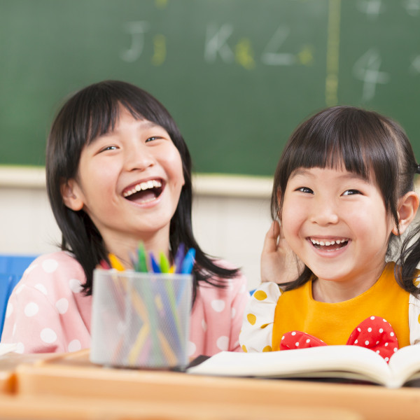 Two primary school girls laughing in class